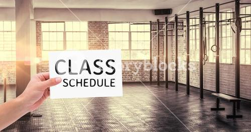 Hand holding placard with text class schedule in the gym