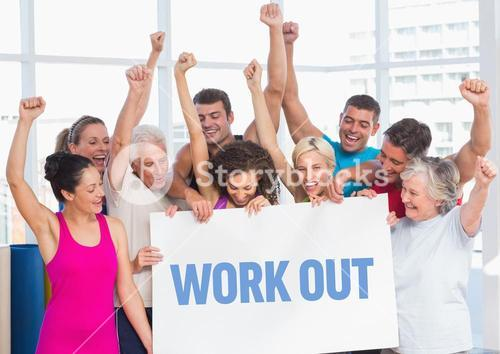 Fitness team standing with placard with work out text in gym