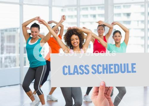 Hand holding placard with class schedule text against women dancing in background