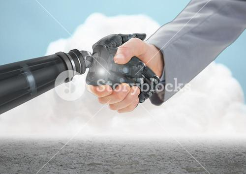 Close-up of businessman shaking hands with robot hand with clouds in background