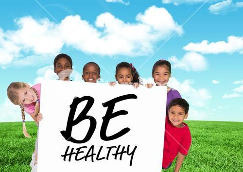 Kids holding card showing text  be healthy in front of blue sky and grass