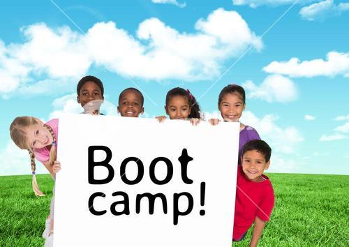 Kids holding card showing text  boot camp in front of blue sky and grass