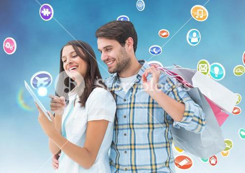 Happy man holding shopping bags and woman using digital tablet with various icons in background