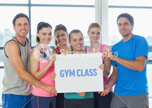 Portrait of group of happy people holding blank placard in gym