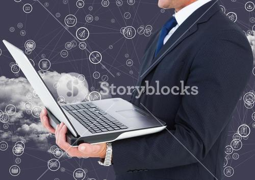 Businessman holding laptop with connecting icons and cloud in background