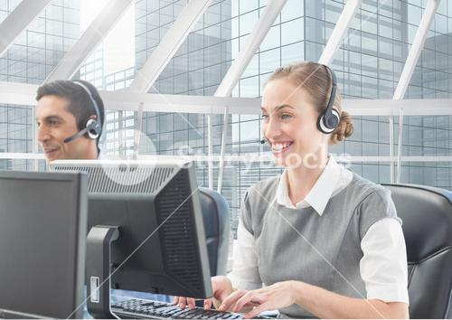 Man and woman talking on headset in customer service office