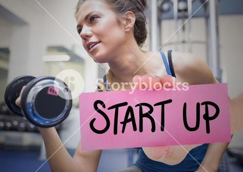 Hand holding placard with text start up and woman exercising with dumbbell in background