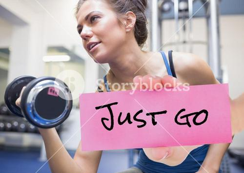 Hand holding placard with text just go and woman exercising with dumbbell in background