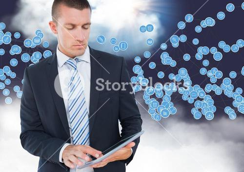 Businessman using digital tablet against technology icons in sky