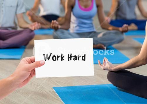 Hand holding placard that reads work hard against people doing meditation