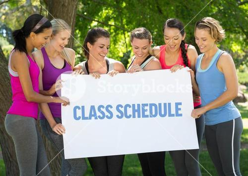 Fit women holding card that reads class schedule