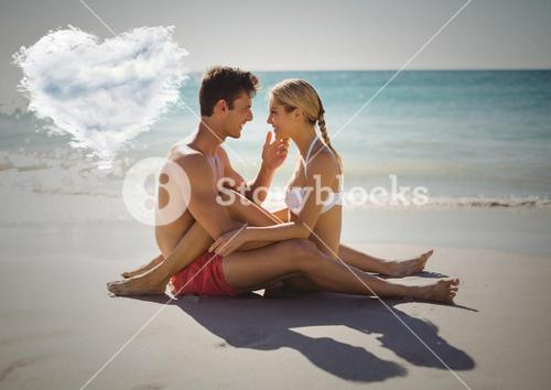 Romantic couple sitting on beach with heart cloud
