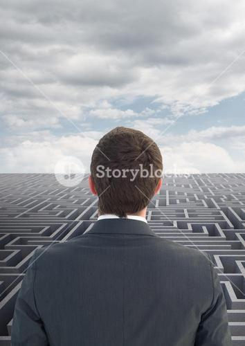 Rear view of business man looking over maze