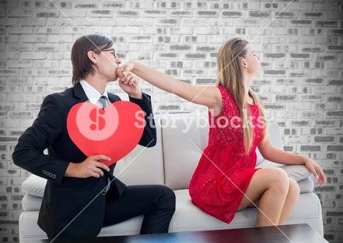 Man holding heart shape kissing on womans hand