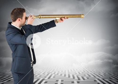 Businessman standing on maze looking through telescope