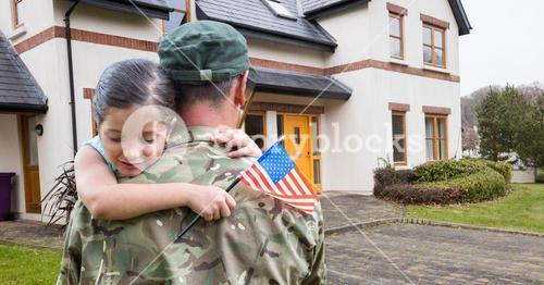 American soldier carrying girl in front of a house