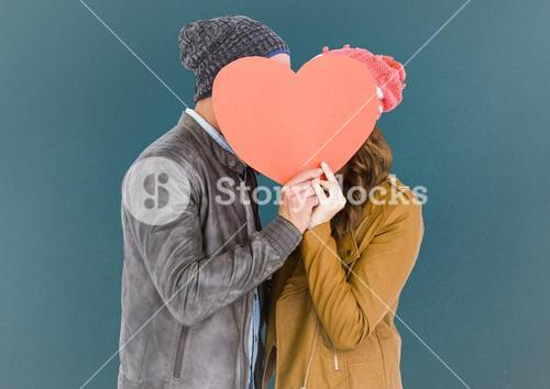 Romantic couple holding heart shape and kissing each other