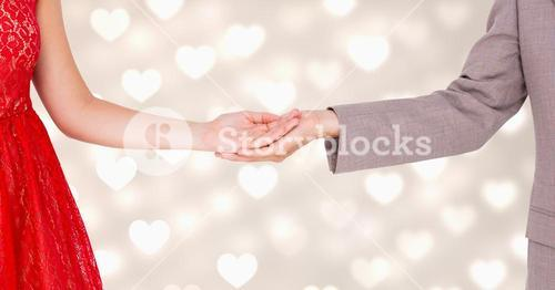 Mid-section of couple standing with hands in hand