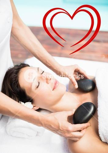 Masseur giving stone massage to woman at spa