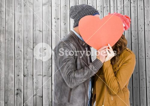Romantic couple hiding their face behind heart