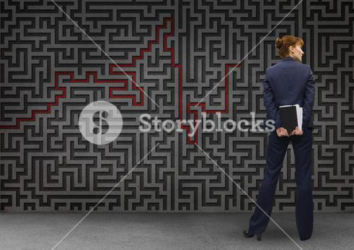 Businesswoman standing in front of maze