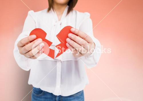 Mid-section of a woman holding a broken heart