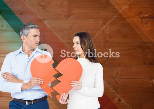 Sad mature couple holding broken heart