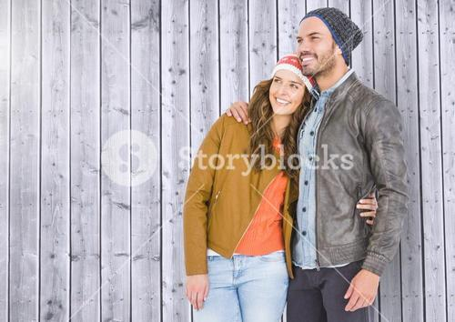 Couple standing against wooden background