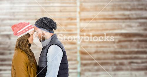 Couple embracing each other against wooden background