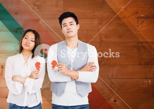 Couple holding broken heart against wooden background