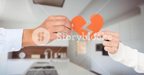 Composite image of business couple hands holding a broken heart