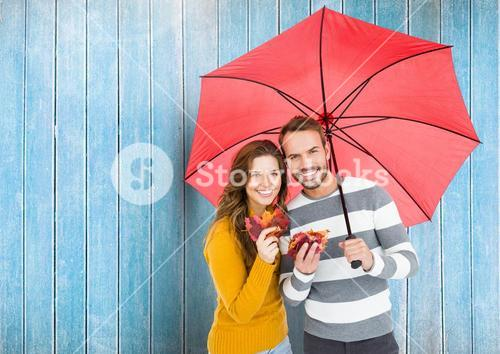 Composite image of happy couple with umbrella