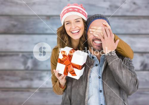 Woman covering mans eyes while gifting