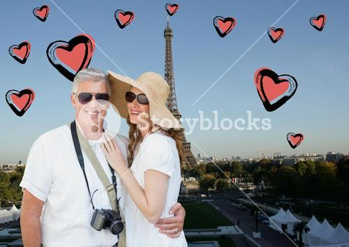 Composite image of couple standing against digitally generated eiffel tower and hearts