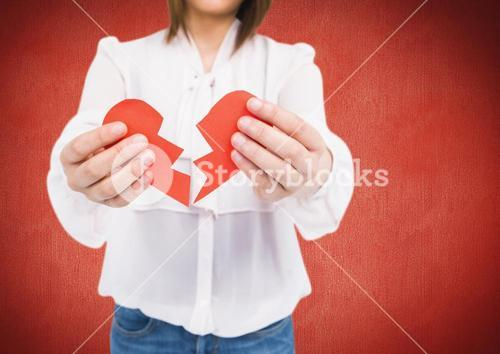 Mid section of woman holding a broken heart