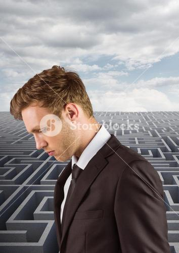 Digital composite image of businessman standing against maze in background