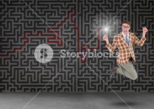 Businessman jumping in front of digitally generated maze wall