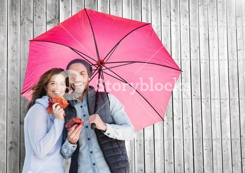 Couple with umbrella against wooden background