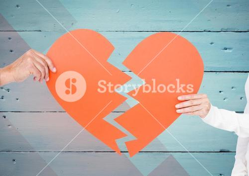 Couple hands holding broken heart against wooden background
