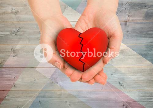 Composite image of hands holding broken heart against wood background