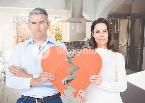 Sad couple holding broken hearts at home