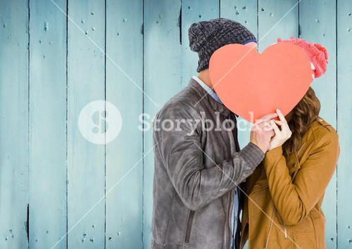 Couple hiding their face behind red heart