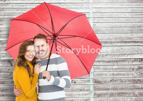 Portrait of happy couple holding umbrella