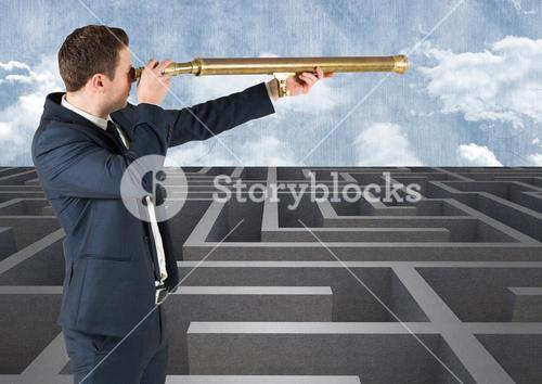 Businessman standing in maze and looking from telescope