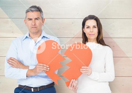 Portrait of sad mature couple holding broken hearts