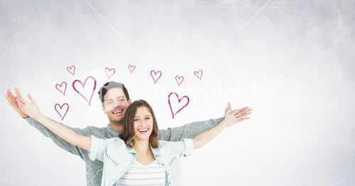 Portrait of couple standing with arms outstretched