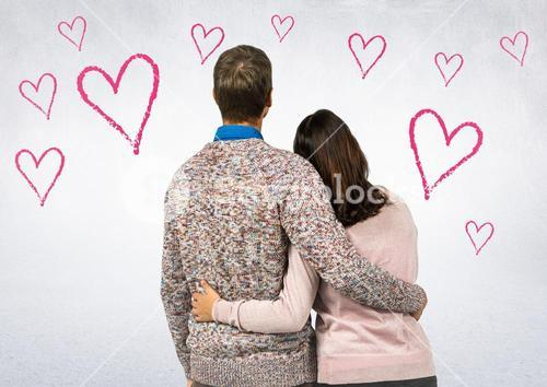 Rear view of couple standing with arm around