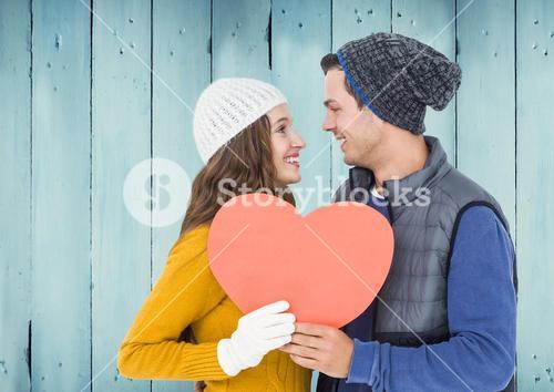 Romantic couple holding heart and looking face to face