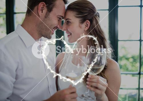 Romantic couple looking face to face and holding glasses of wine