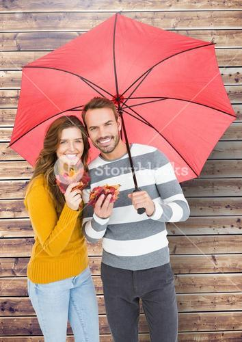 Portrait of happy couple holding umbrella and maple leaves